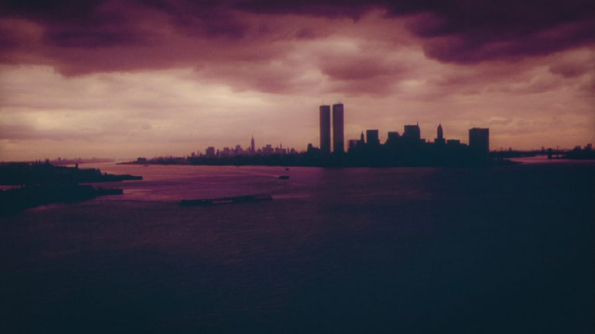 Image of the NY skyline with the Twin Towers in silhouette, in a dark, cloudy sky.
