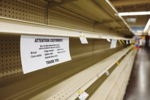 A photo of empty store shelves with a note to customers apologizing for the missing inventory due to COVID-19.