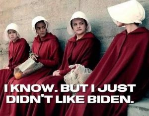 A group of women in Handmaid garments with text that says I know. But I just didn't like Biden.